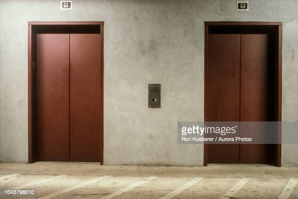 two closed elevator doors - koeberer stock photos and pictures