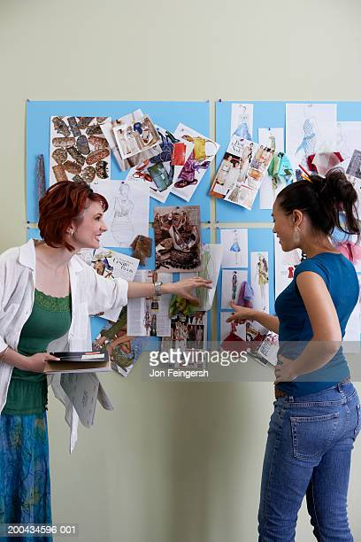 Two clothing designers looking at sketches
