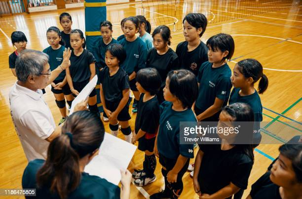 two coaches giving advice and instruction to young girls during a team volleyball practice - team photo ストックフォトと画像