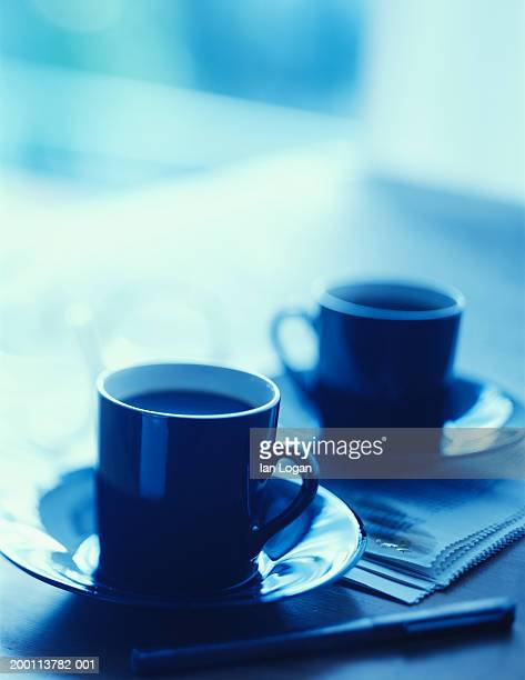 two coffee cups and newspaper on table (focus on cup in foreground) - two objects stock pictures, royalty-free photos & images