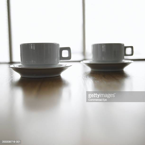 Two coffee cups sitting on table, close-up
