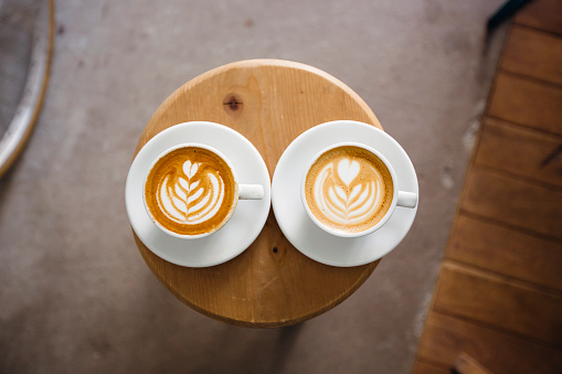 Two coffee cups with latte art on a round wooden table, directly above - gettyimageskorea