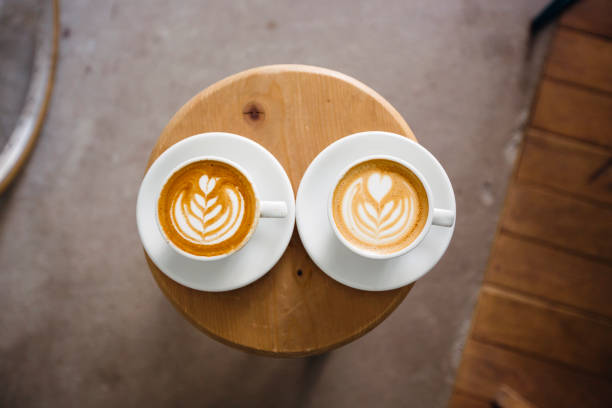 two coffee cups with latte art on a round wooden table, directly above - 對稱 個照片及圖片檔