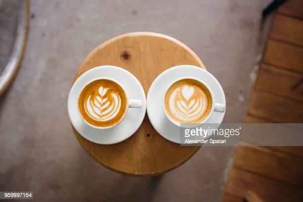 two coffee cups with latte art on a round wooden table, directly above - symmetry stock photos and pictures