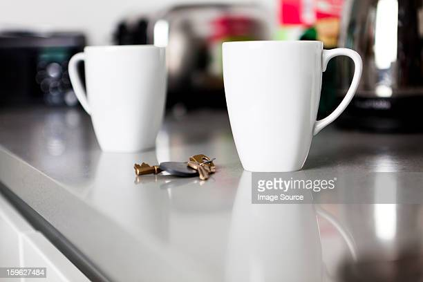 Two coffee mugs with keys on kitchen counter