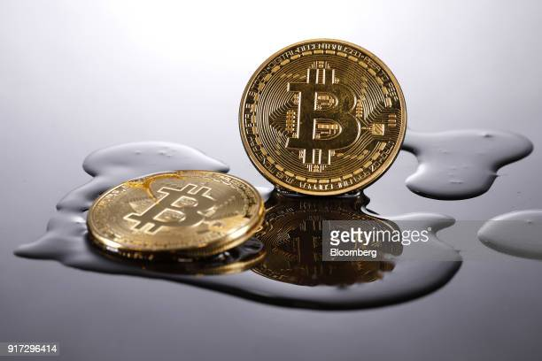 Two coins representing Bitcoin cryptocurrency are reflected on a polished surface as they sit in a pool of translucent liquid in this arranged...