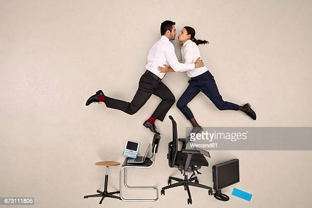 Two colleages balancing on chairs and kissing