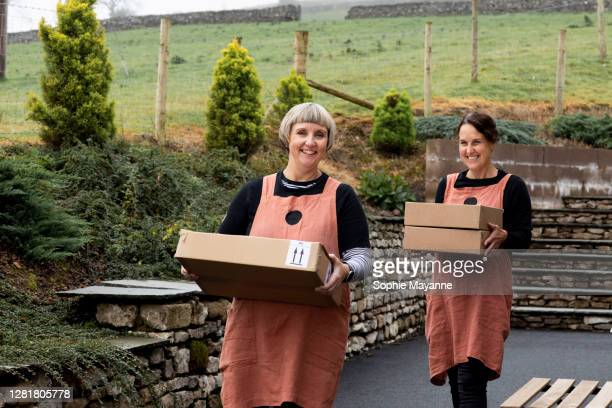 two colleagues at a bakery carrying boxes ready for delivery - femalefocuscollection stock pictures, royalty-free photos & images