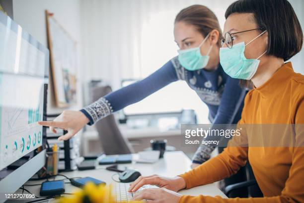 two colleagues at work wearing face protective mask, to protecting themselves against corona virus - infectious disease stock pictures, royalty-free photos & images
