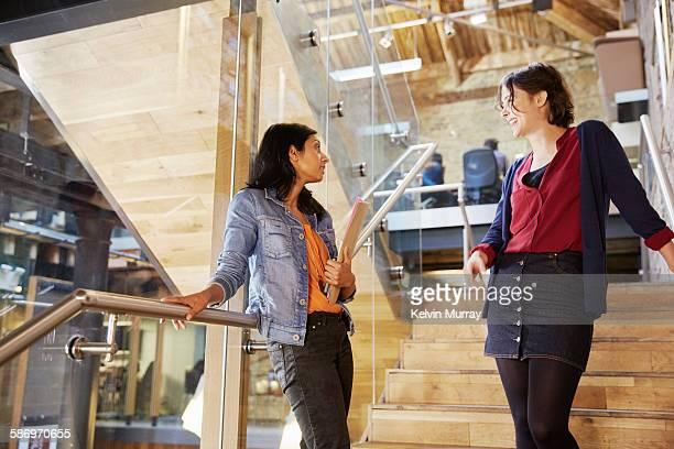 Two colleagues chat on stairs in modern office