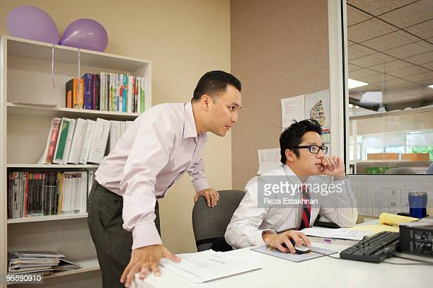 Two colleagues check monitor for information