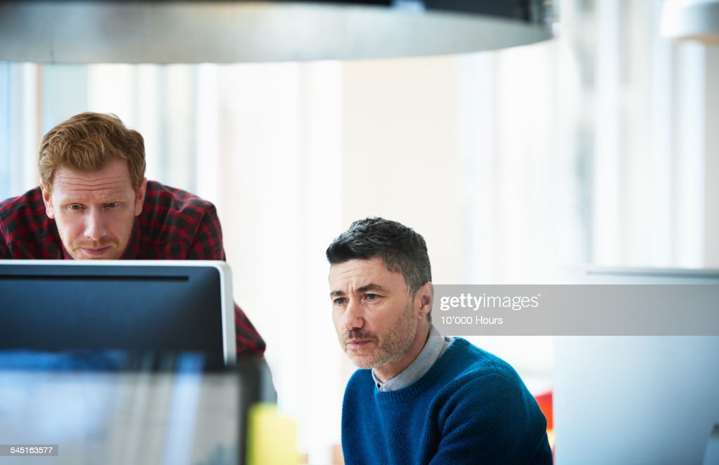 Two colleagues contemplating a project on computer : Stock Photo