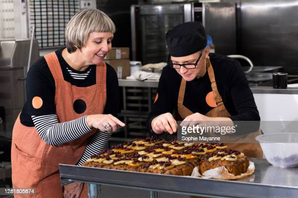 two colleagues decorating fresh cake in a commercial kitchen - femalefocuscollection stock pictures, royalty-free photos & images