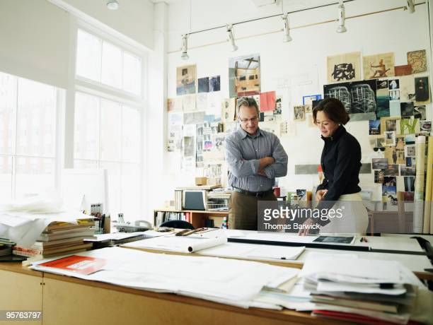 two colleagues discussing plans at desk - leanintogether stock pictures, royalty-free photos & images