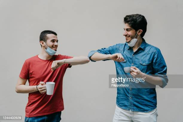 two colleagues greeting each other with an elbow bump during a coffee break - elbow bump stock pictures, royalty-free photos & images