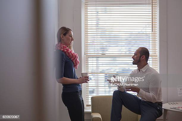 Two colleagues having a discussion in office with coffee