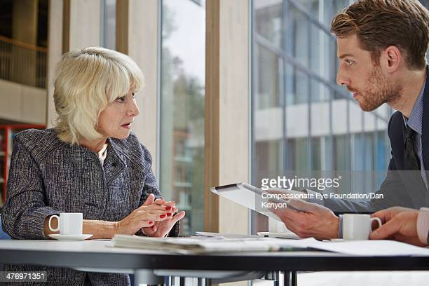 two colleagues in conversation in meeting - mid adult stock pictures, royalty-free photos & images
