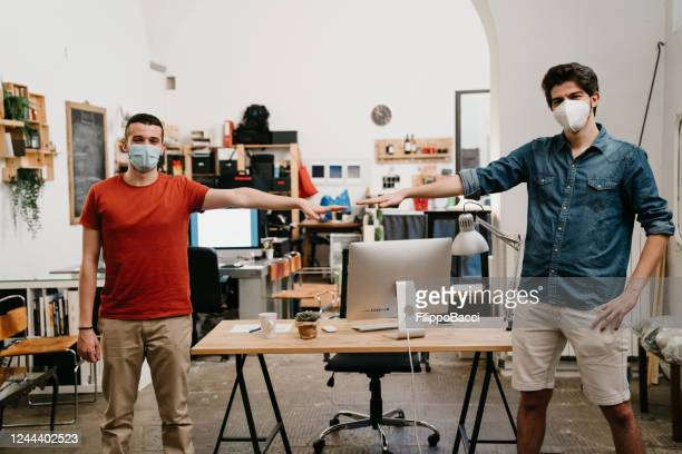 two colleagues maintaining physical distance in the office - opening event stock pictures, royalty-free photos & images