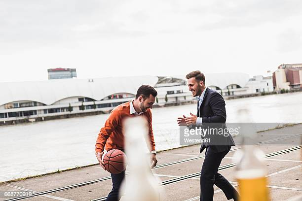 Two colleagues playing basketball after work and having a beer