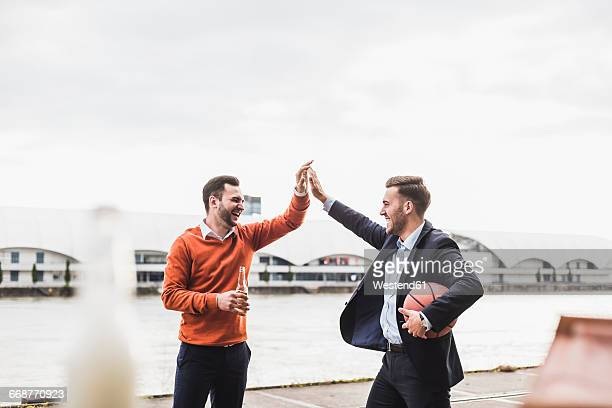 Two colleagues playing basketball after work, giving high five