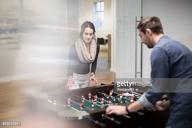 Two colleagues playing foosball in office break room