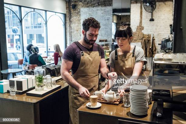 Two colleagues preparing tray of drinks in cafe