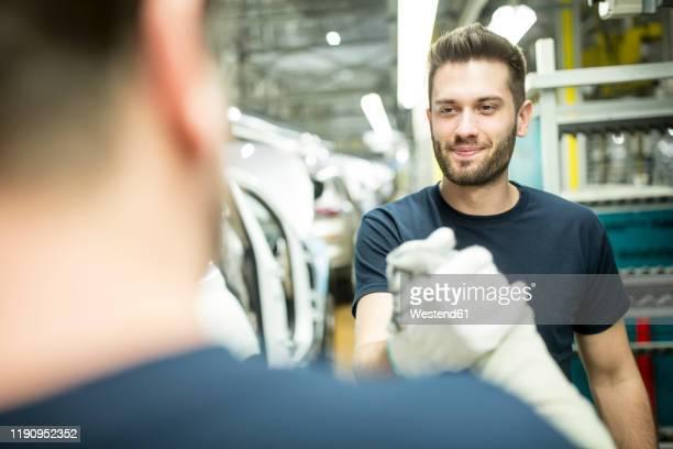 two colleagues shaking hands in modern car factory - rechnerunterstütztes konstruieren stock-fotos und bilder