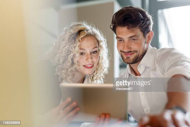 Two colleagues sharing tablet in office