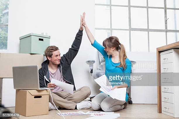 Two colleagues sitting on ground between cardboard boxes in an office giving high five