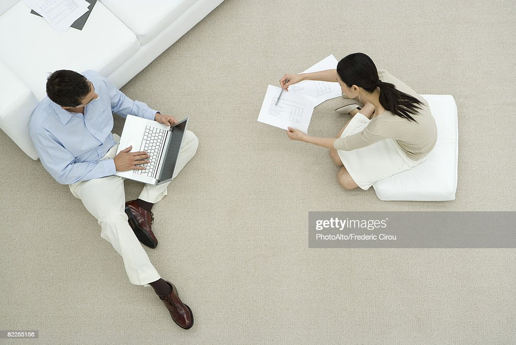 Two colleagues sitting on the ground, discussing document, overhead view : Stock Photo
