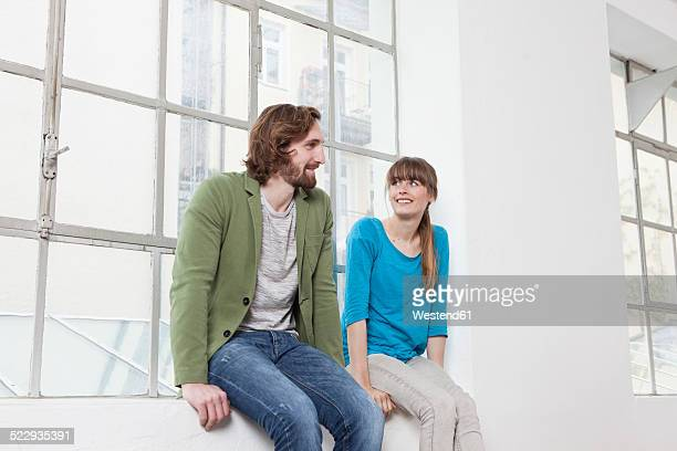 Two colleagues sitting on window sill in an office