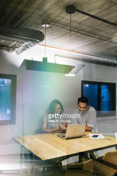 Two Colleagues Smiling, Looking Over Work On A Laptop