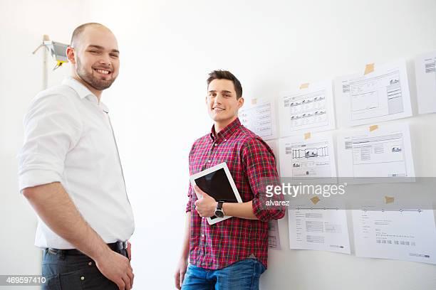 Dois colegas de trabalho em pé no escritório