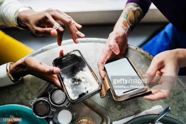 two colleagues swapping contact information in cafe - freundschaftliche verbundenheit stock-fotos und bilder