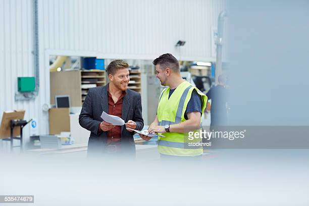 Two colleagues talking to one another at factory