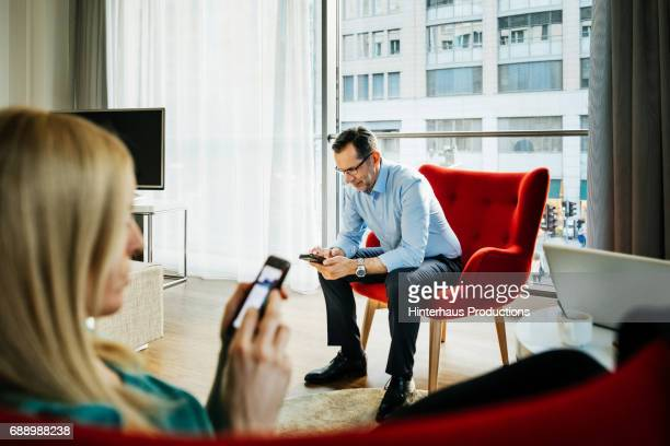 Two Colleagues Using Their Phones In Hotel Room