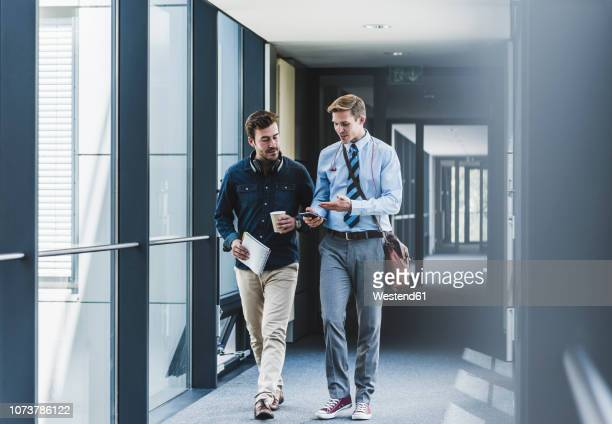 two colleagues walking and talking on office floor - business finance and industry stock pictures, royalty-free photos & images