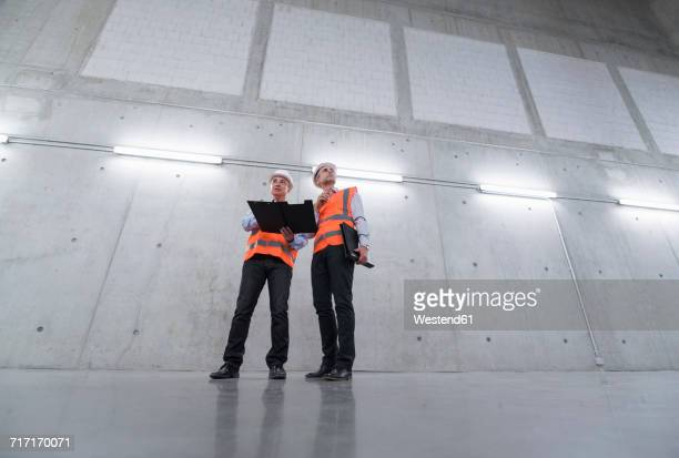 two colleagues wearing safety vests and hard hats talking in a building - weitwinkelaufnahme stock-fotos und bilder