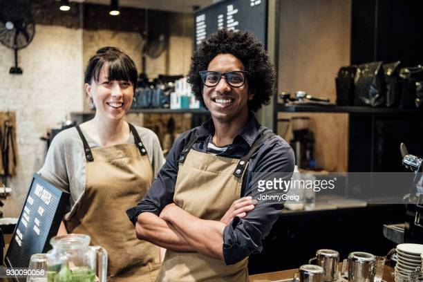 Two colleagues working in coffee shop smiling towards camera