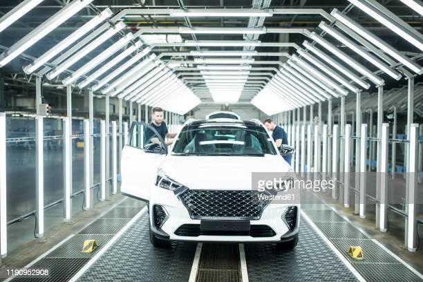 two colleagues working in modern car factory - rechnerunterstützte fertigung stock-fotos und bilder