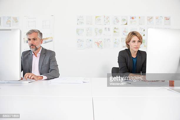 two colleagues working side by side in an office - side by side stock pictures, royalty-free photos & images