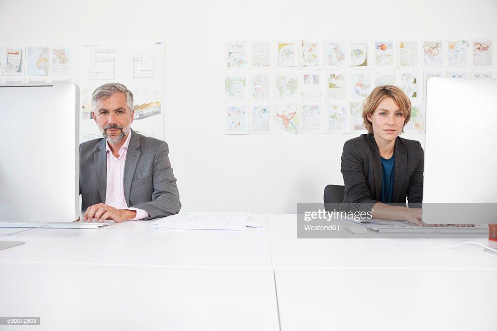 Two colleagues working side by side in an office : Foto de stock