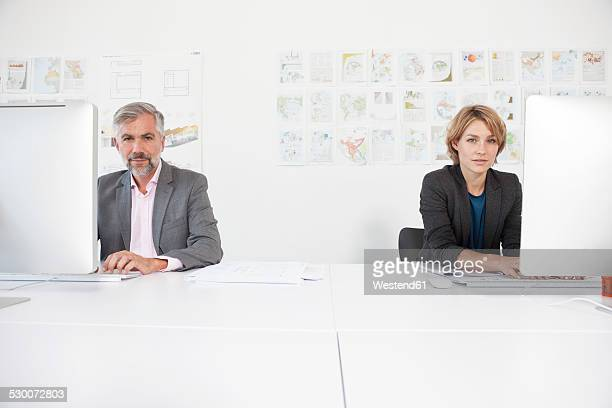 Two colleagues working side by side in an office