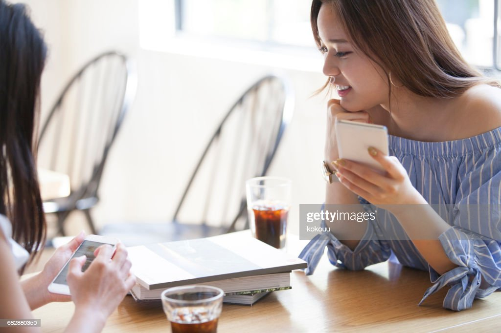 Two college girls spend a quiet morning at a cafe. : Stock Photo