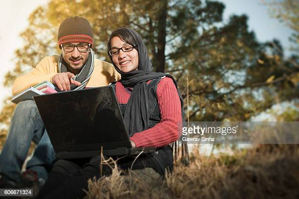 two college students are using laptop together in hilly area. - indian college girls stockfoto's en -beelden