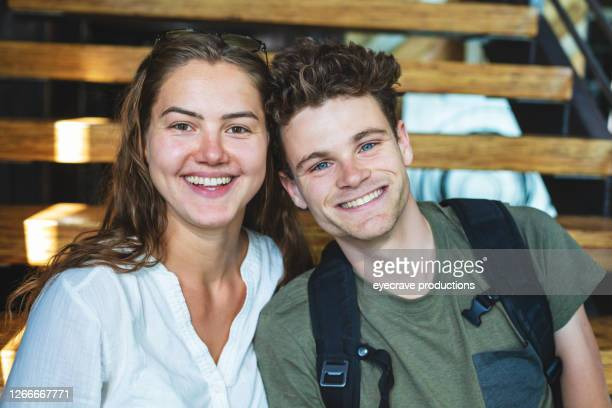 two college students female and male sitting together on stairs - eyecrave  stock pictures, royalty-free photos & images