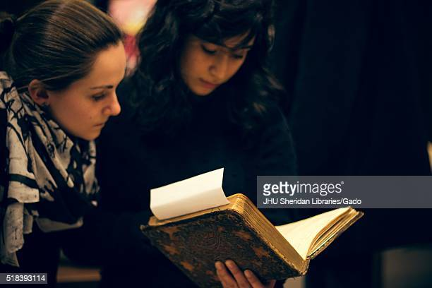 Two college students holding and reading an antique book, 2016. Courtesy Eric Chen. .