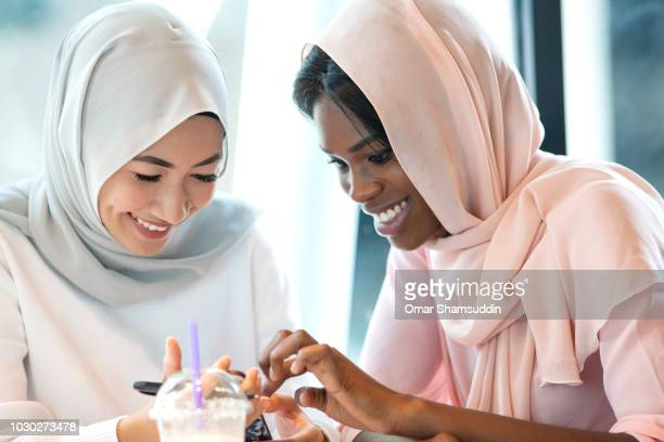 Two college students in hijab having fun with the smart phone