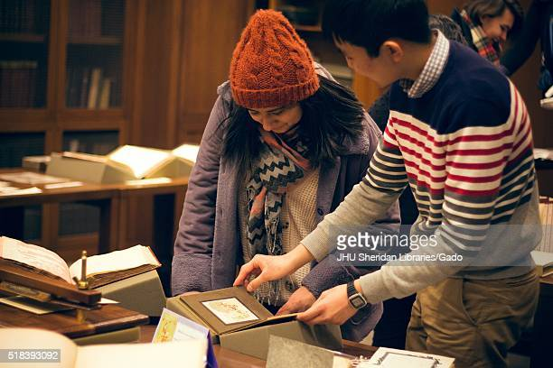 Two college students one male and one female observing a collection of 'dirty' erotic rare books in the Special Collections department of the Johns...