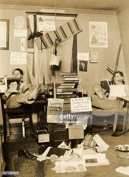 Two college students relax in their accomodation amidst a proliferation of tongueincheek signs February 1926